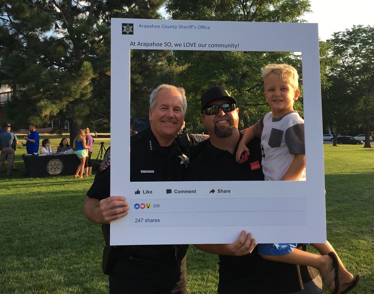 Sheriff Walcher poses for photo with a ,am and his son