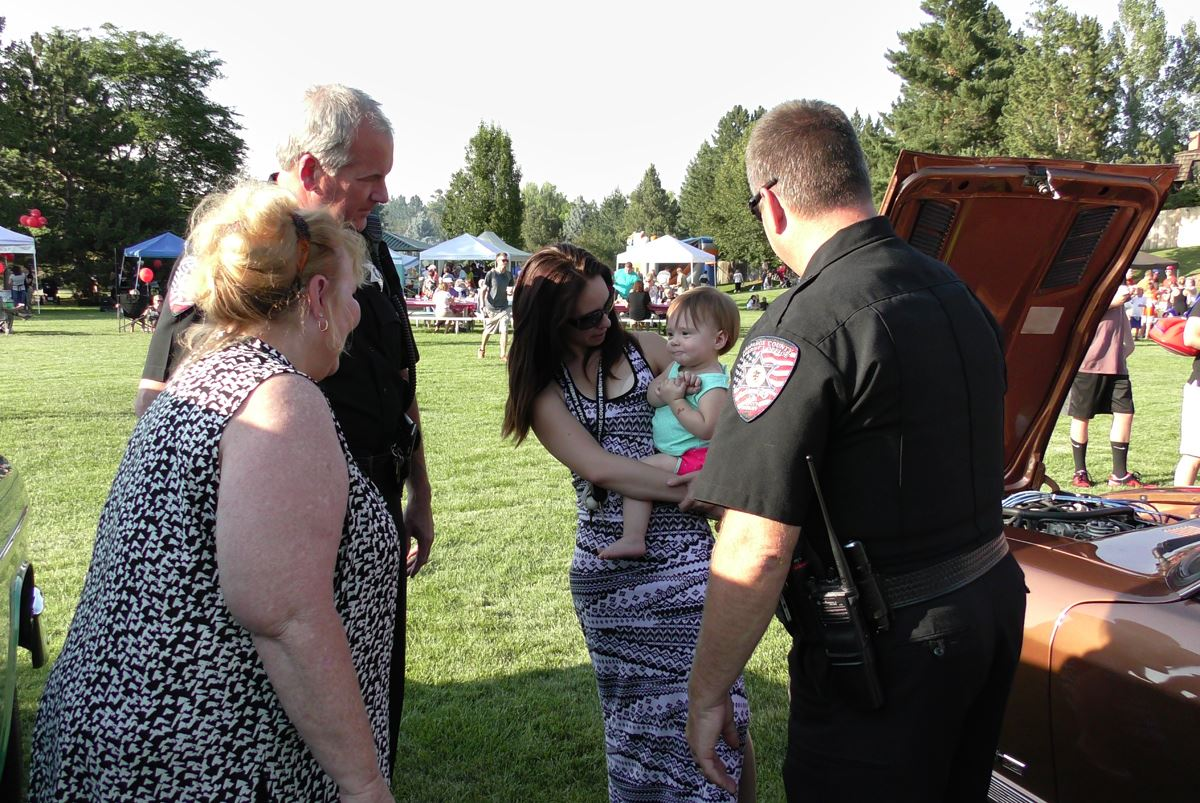 Sheriff Walcher and Deputy Brian McKnight talk with two women and a small child at National Night Ou