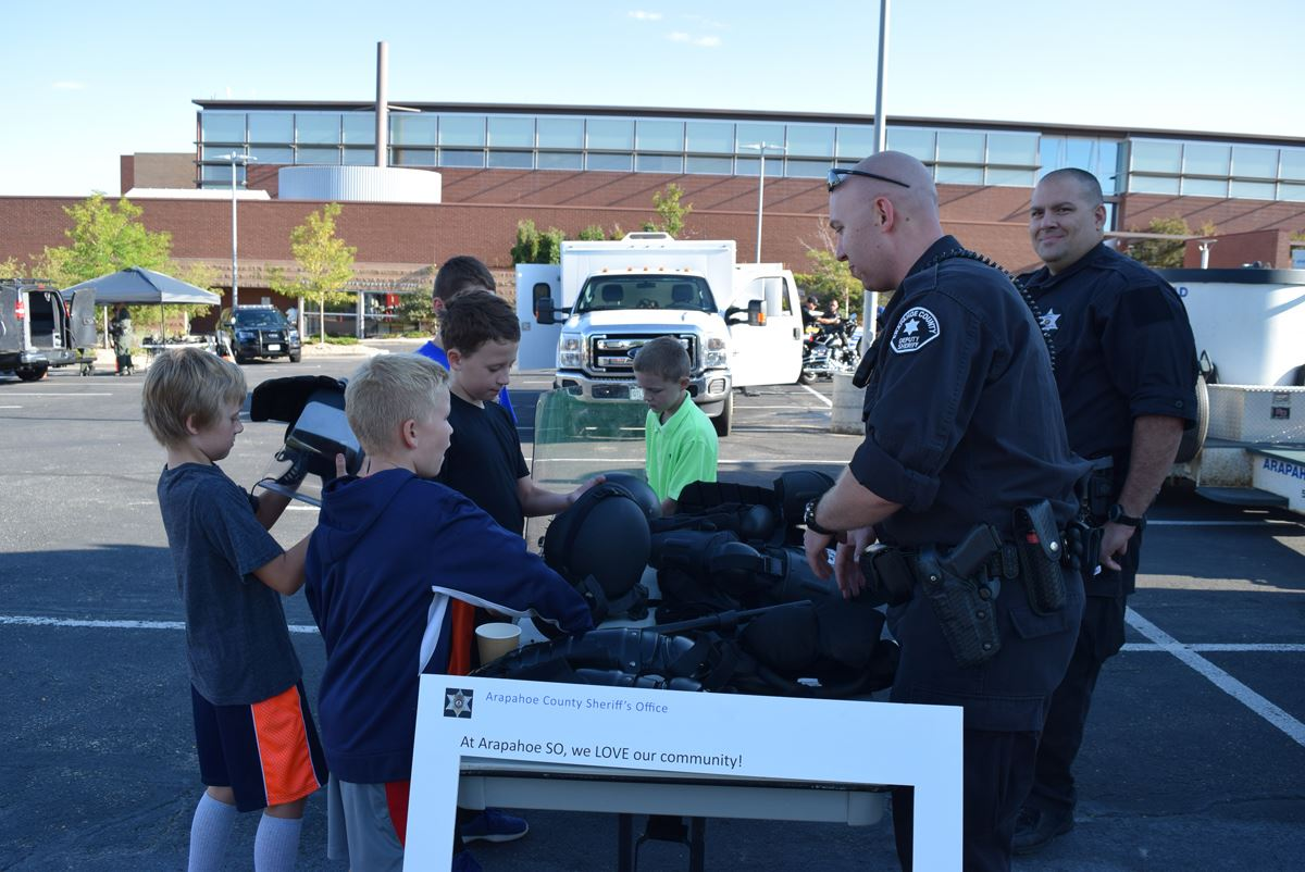 Several children talk with jail deputies and touch the special gear used by SORT
