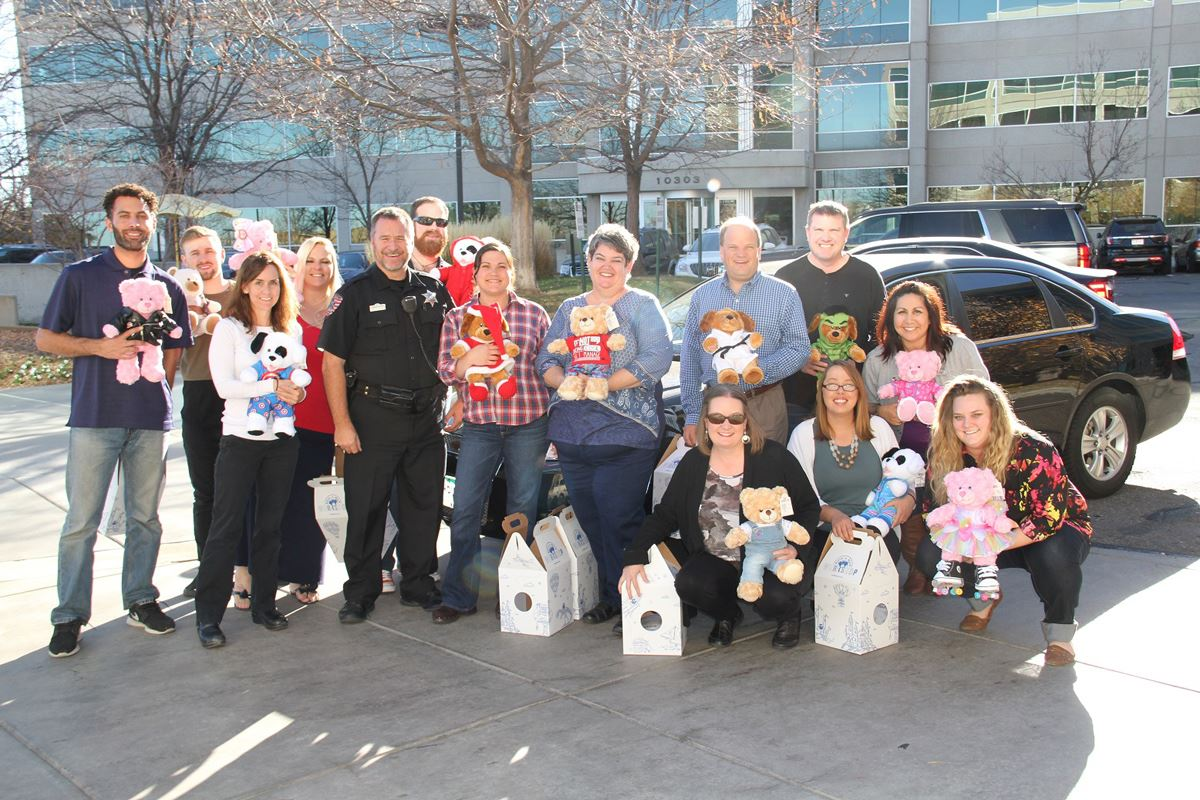 Private group poses with stuffed bears they donated to the toy drive