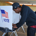Male voter fills out ballot at voting booth