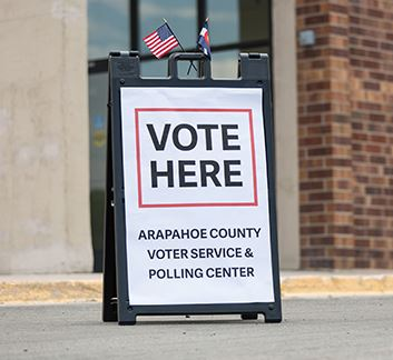 A sign stands outside a brick building displaying the words Vote Here. Arapahoe County Voter Service