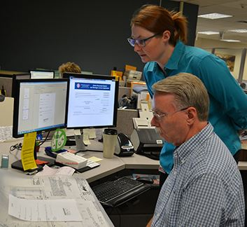 Two Arapahoe County Recording Division employees review a land survey.