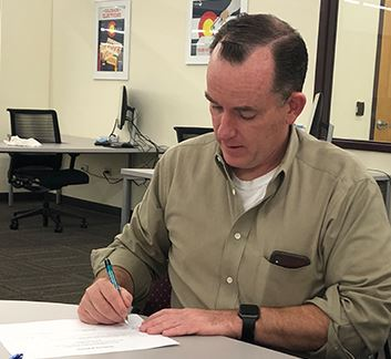 Clerk and Recorder Matt Crane signs the Certificate of Election for the 2018 Primary Election.
