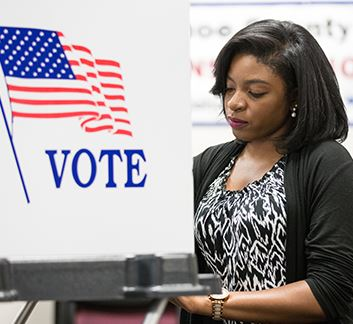 Female voter sits at a voting booth
