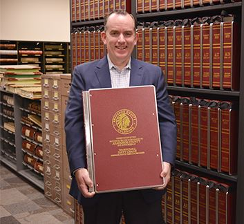 Clerk and Recorder Matt Crane holds a newly preserved record book Opens in new window