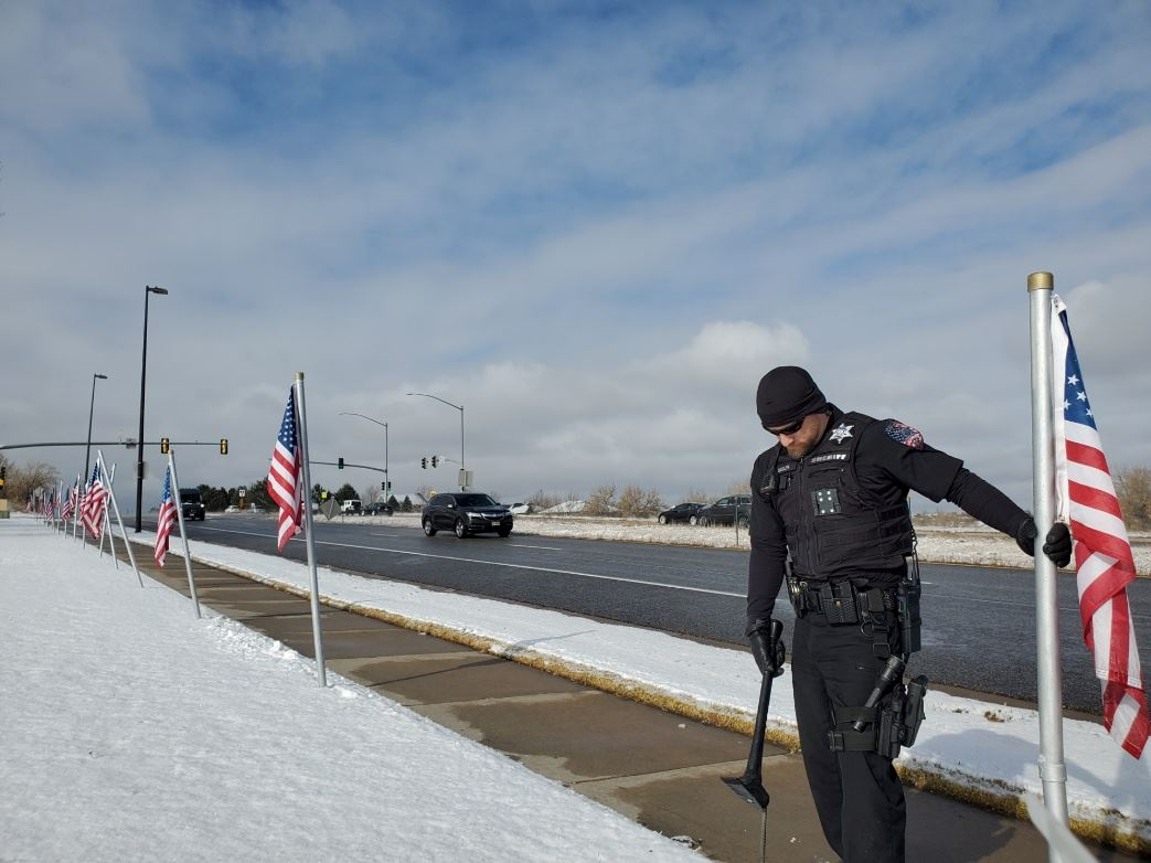 Deputy Ben Sadler fixes flags at Grand View High
