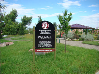Image showing the park from the entrance. Park sign in foreground and picnic pavilion in background.