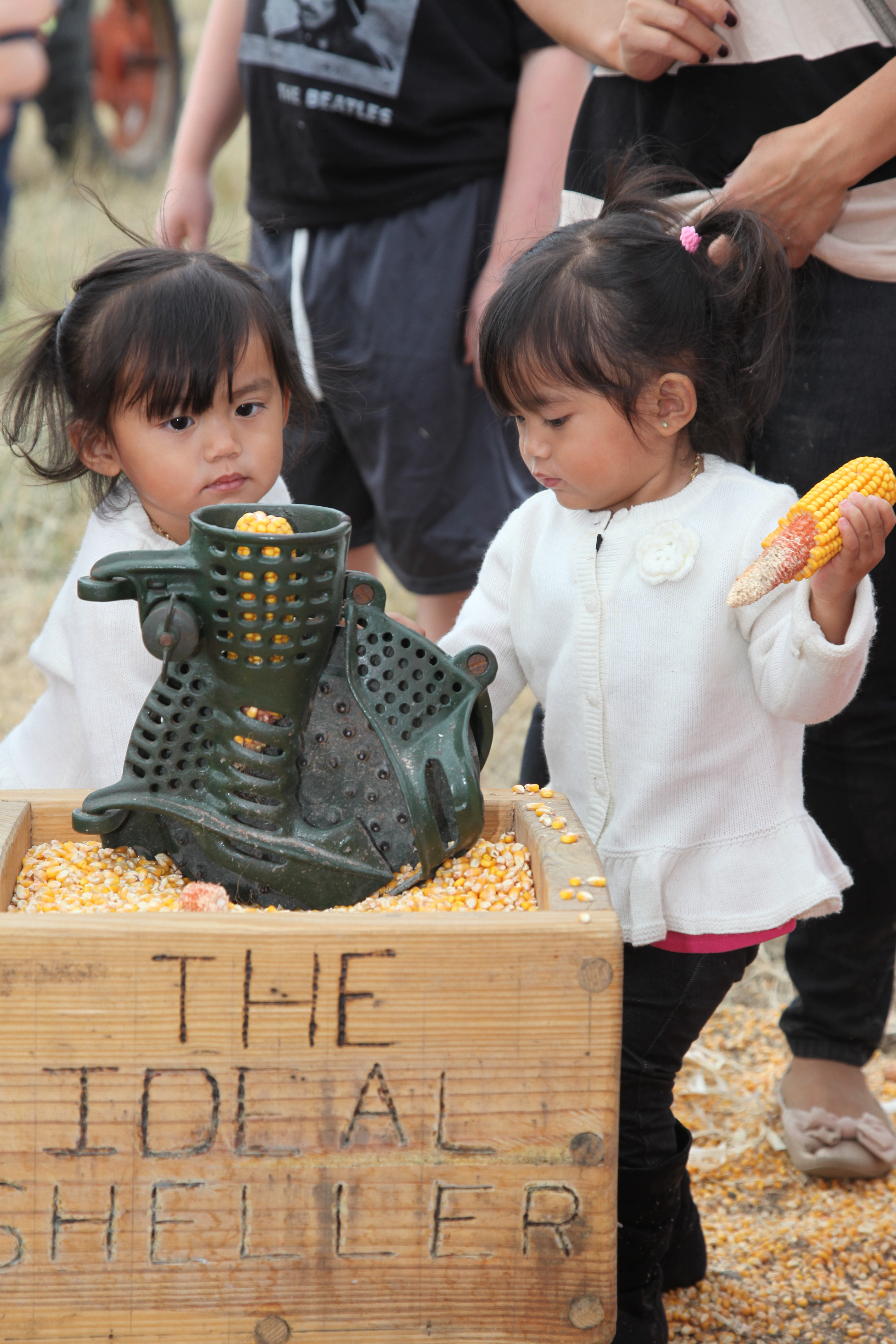 2 small girls try corn milling