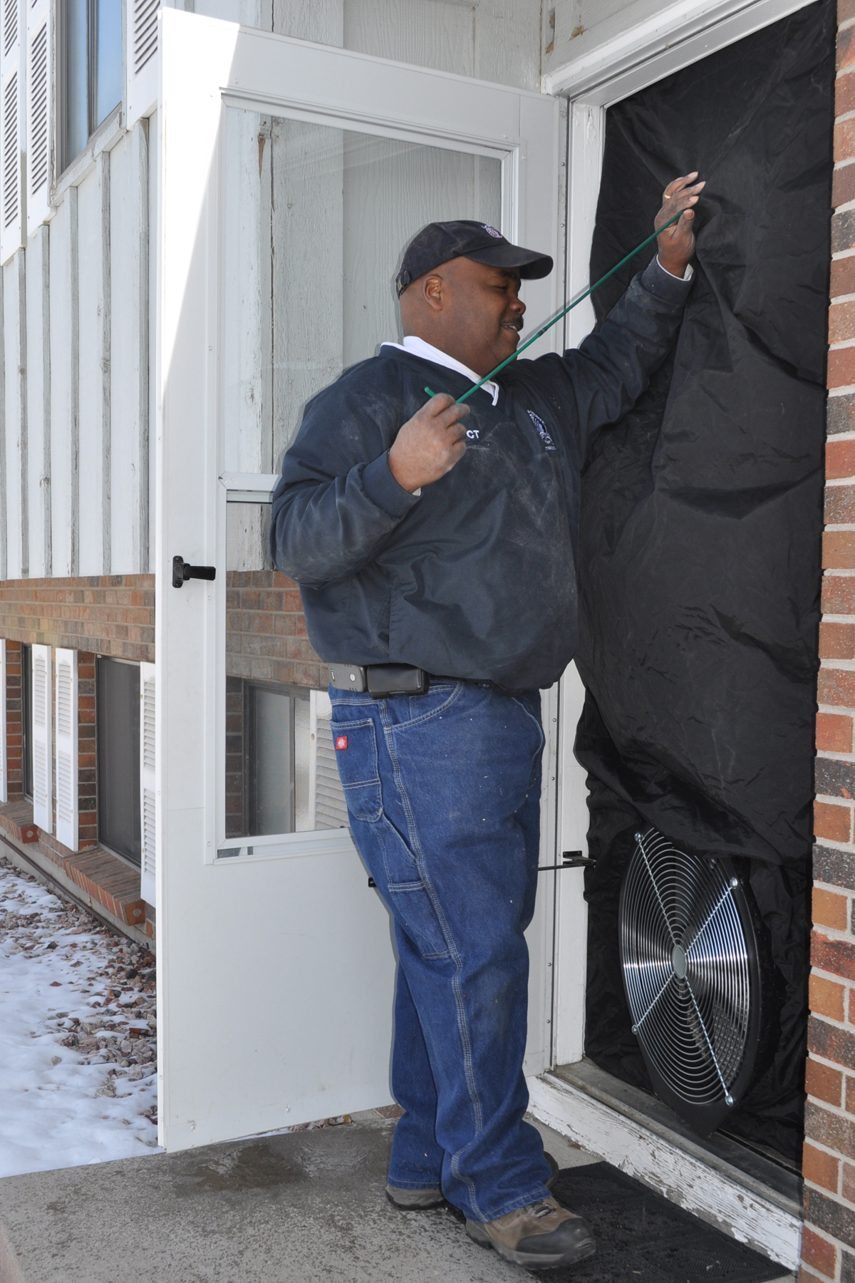 Weatherization tech conducts a blower door test